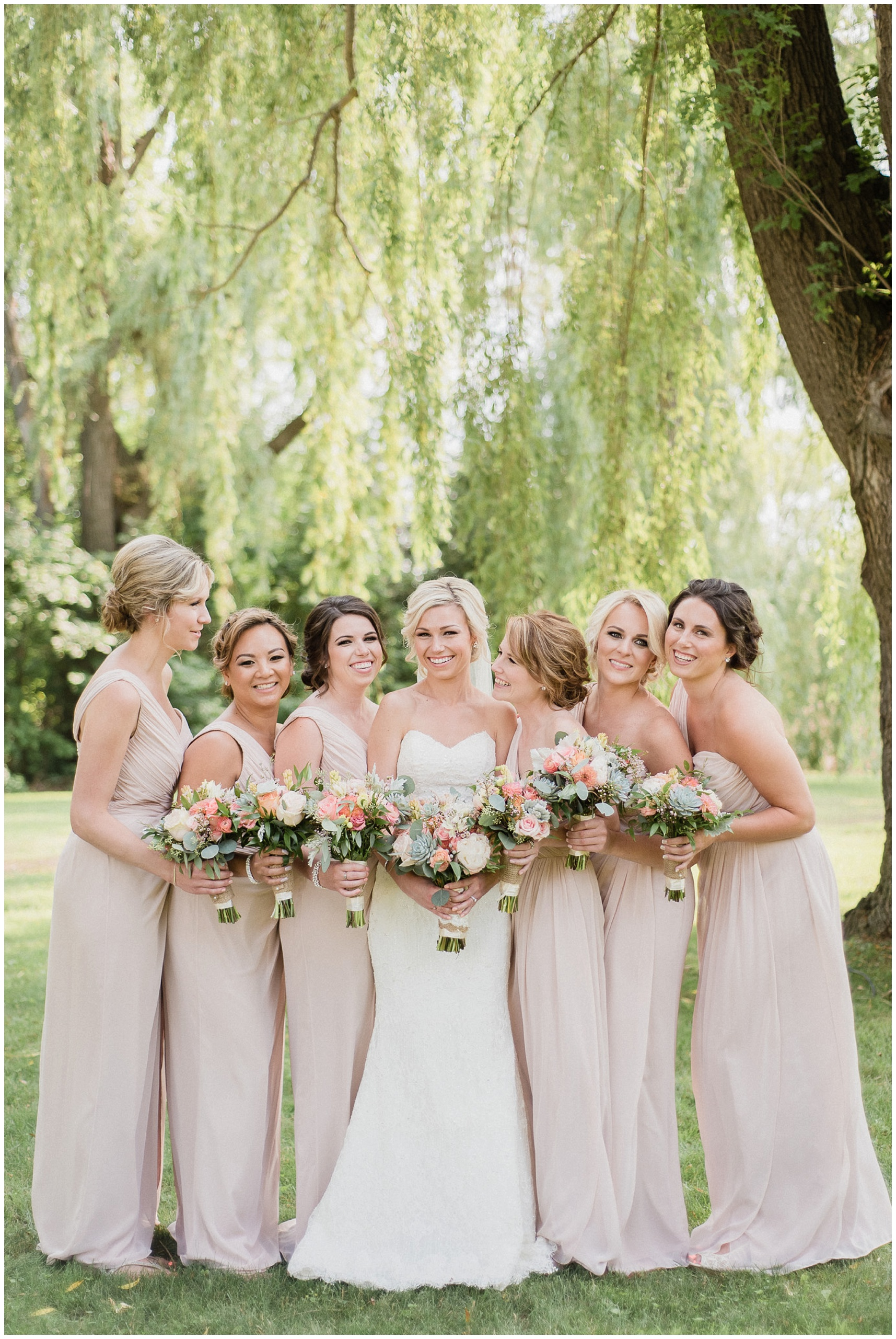 Candid bridesmaids photo with blush pink one shouldered, full length bridesmaid dresses. Photographed by Jenn Kavanagh Photography