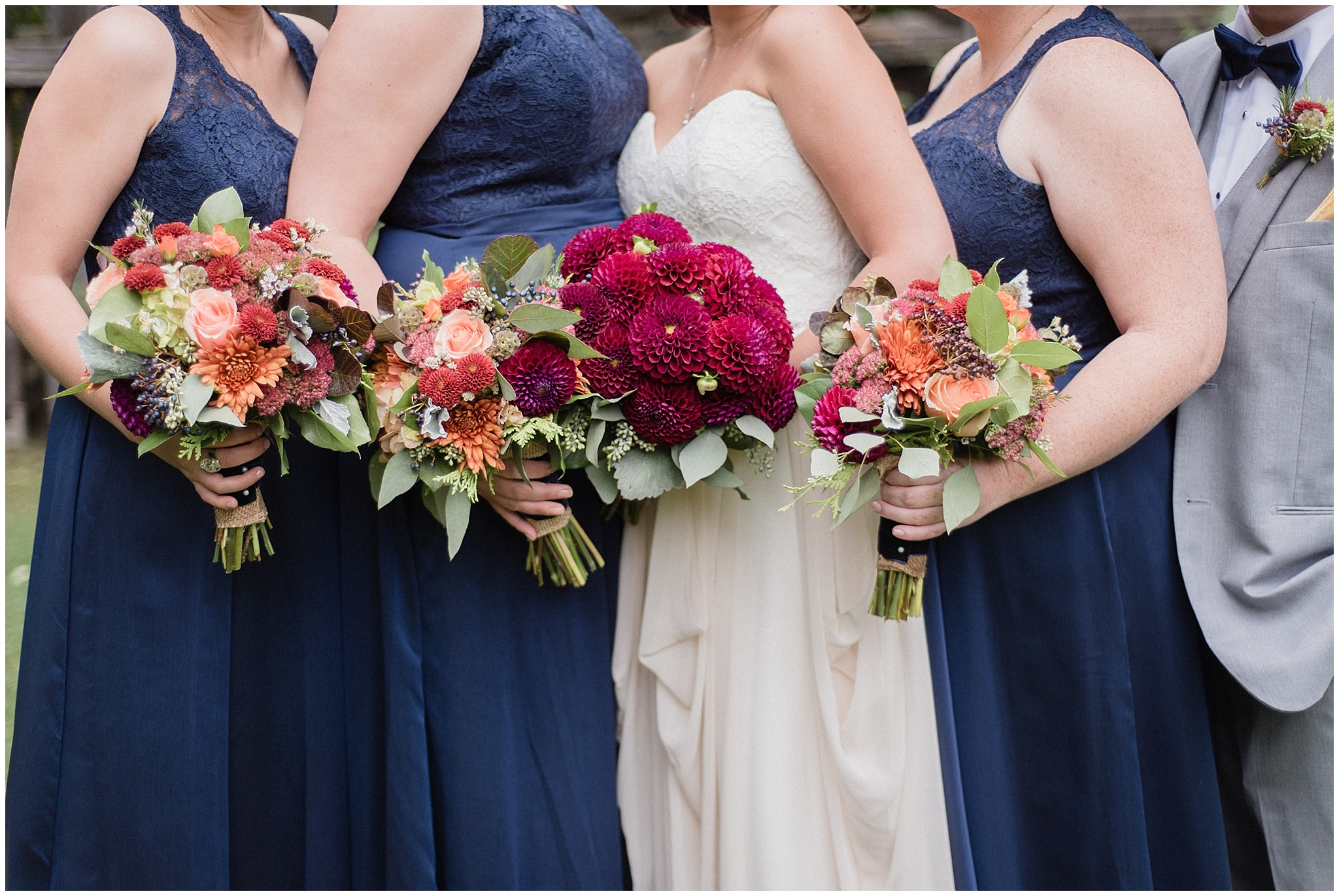 LazyDayz Bed & Breakfast wedding featuring navy blue bridesmaids dresses with orange and red florals by Jenn Kavanagh Photography