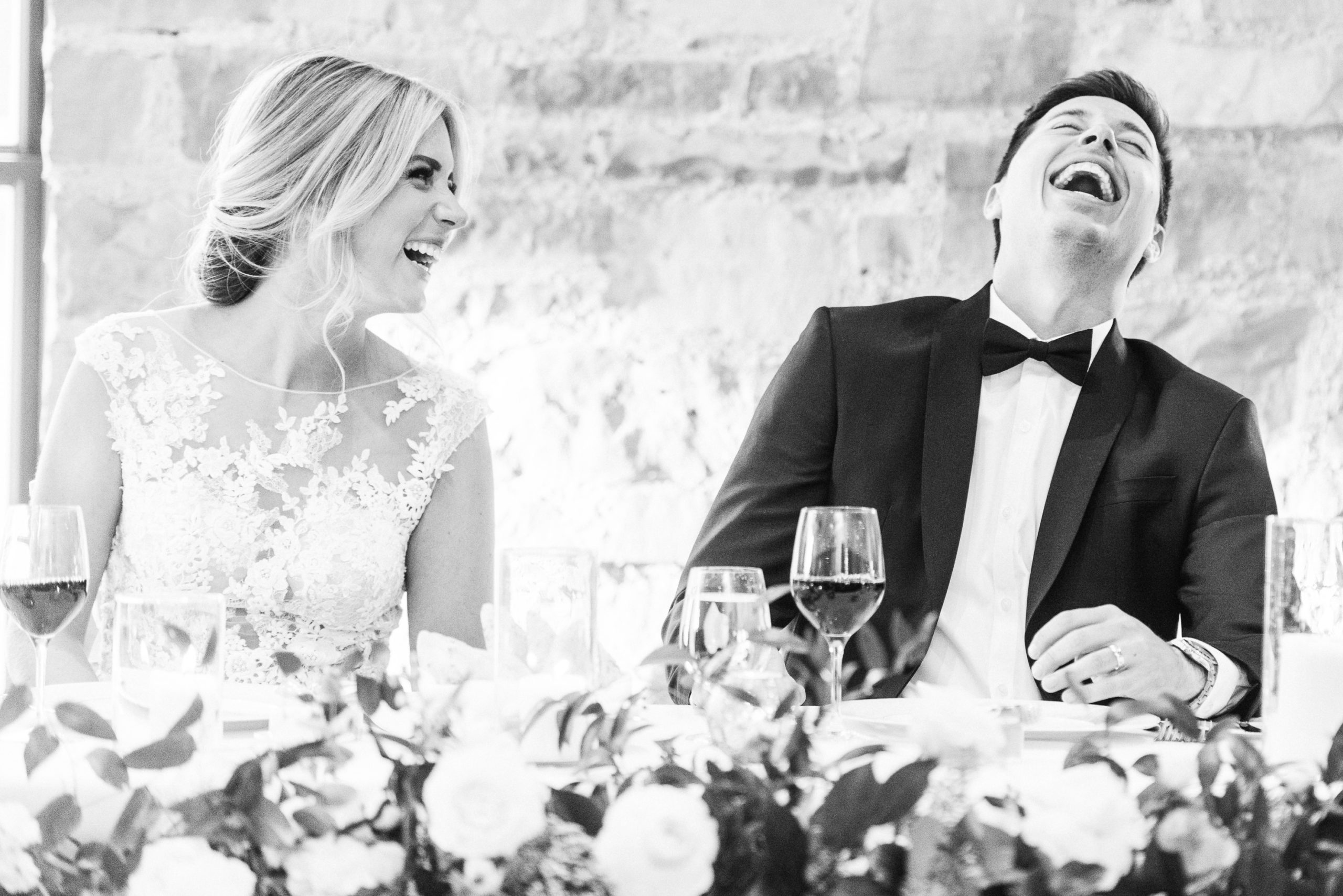 Black and white candid image of newlyweds at the Elora Mill